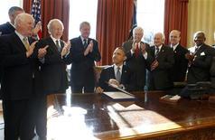 """Президент США Барак Обама подписывает """"закон Магнитского"""" 14 декабря 2012 года. Администрация Обамы в пятницу опубликовала список из 18 человек, подозреваемых в нарушении прав человека в России, выполняя требование закона, названного в честь умершего в тюрьме юриста Сергея Магнитского. REUTERS/Larry Downing"""