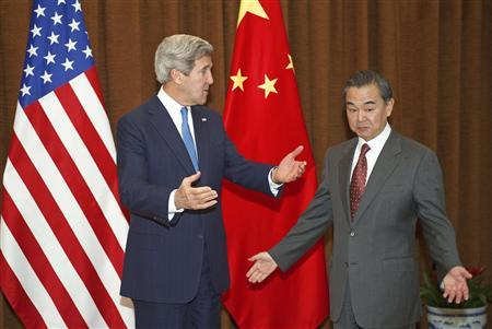 U.S. Secretary of State John Kerry gestures next to China's Foreign Minister Wang Yi (R) at the Chinese Ministry of Foreign Affairs in Beijing April 13, 2013. REUTERS/Paul J. Richards/Pool