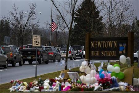 Cars drive below a U.S. flag at half mast and past a memorial outside the entrance to Newtown High School in Newtown, Connecticut December 18, 2012. REUTERS/Lucas Jackson
