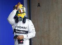 Piloto de F1 da equipe Mercedes Lewis Hamilton acena ao celebrar a conquista da pole position no treino oficial para o Grande Prêmio da China de F1, no Circuito Internacional de Xangai. É a primeira pole position para a Mercedes na Fórmula 1, na China, com Kimi Raikkonen da Lotus em segundo e a Red Bull bem abaixo do potencial. 13/04/2013. REUTERS/Carlos Barria