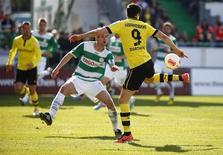 Robert Lewandowski, do Borussia Dortmund dribla Thomas Kleine, do Greuther Fürth, durante partida pela primeira divisão do Campeonato Alemão, em Fürth. O Borussia Dortmund marcou cinco gols ainda no primeiro tempo e impôs uma vitória de 6 x 1 ao lanterna Greuther Fürth. 13/04/2013. REUTERS/Kai Pfaffenbach