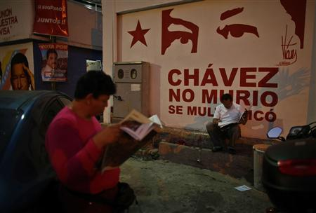 Members of the Venezuela's acting president and presidential candidate Nicolas Maduro campaign team, or 'Commando Hugo Chavez', read newspapers outside their headquarters at the 23 de Enero neighbourhood in Caracas April 12, 2013. REUTERS/Tomas Bravo