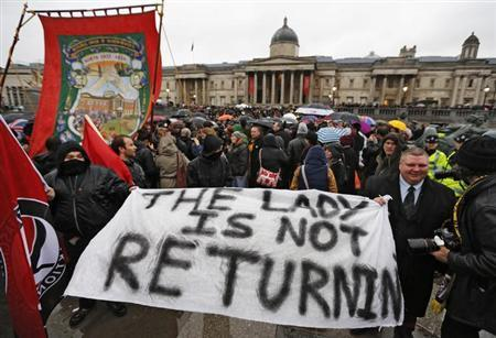 Revellers hold up a banner as they join an outdoor party celebrating the death of former British prime minister Margaret Thatcher, at Trafalgar Square in central London April 13, 2013. REUTERS/Chris Helgren