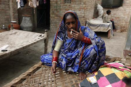 lalee Kolhi, a freed bonded labourer turned activist, smokes a cigarette while she sits on a bed at her home on the outskirts of the city of Hyderabad in Pakistan's Sindh province February 4, 2013. REUTERS/Akhtar Soomro