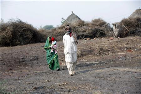 Bhagat and his wife walks to their hut at a rescue camp for the freed bonded laborers on the outskirts of the city of Hyderabad in Pakistan's Sindh province February 5, 2013. REUTERS/Akhtar Soomro