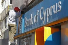 A worker paints a wall above a branch of Bank of Cyprus in Bucharest April 1, 2013. REUTERS/Bogdan Cristel