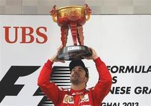 Piloto da equipe Ferrari de F1 Fernando Alonso ergue o troféu pela vitória no Grande Prêmio da China, no Circuito Internacional de Xangai. Fernando Alonso venceu de forma dominante o GP da China, neste domingo, com uma ótima estratégia que proporcionou à Ferrari a primeira vitória na temporada de Fórmula 1 e pressionou a atual campeã Red Bull. April 14, 2013. REUTERS/Kim Kyung-Hoon