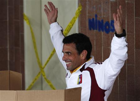 Venezuelan opposition leader and presidential candidate Henrique Capriles gestures from inside a voting booth, while voting for the successor to late President Hugo Chavez, in Caracas April 14, 2013. REUTERS/Tomas Bravo