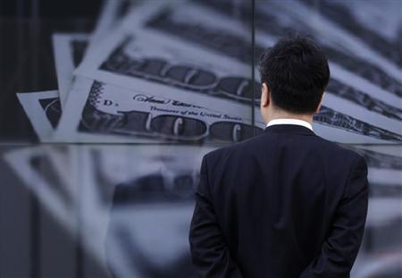 A businessman looks at a screen displaying a photo of U.S. 100 dollar bank notes in Tokyo April 8, 2013. REUTERS/Toru Hanai