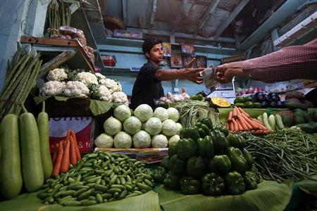 A vendor accepts money from a customer at his vegetable stall at a wholesale fruit and vegetable market in Mumbai April 14, 2013. REUTERS/Vivek Prakash