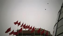 Китайские флаги развиваются на крыше Дома народных собраний в Пекине, 2 марта 2010 года. Рост экономики Китая неожиданно замедлился в первом квартале до 7,7 процента с 7,9 процента в четвертом квартале 2012 года, сообщило в понедельник Национальное статистическое бюро. REUTERS/Petar Kujundzic