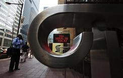 People walk by a sign displaying TSX information in Toronto, August 17, 2009. REUTERS/Mark Blinch