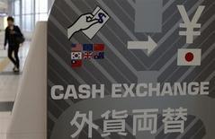 Женщина проходит мимо аппарата обмена валют в аэропорту Ханеда в Токио 5 апреля 2013 года. Курс доллара отступил от пика четырех лет к иене после того, как США напомнили Японии о ее обещании воздерживаться от политики, направленной на искусственное ослабление иены. REUTERS/Toru Hanai