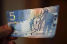 A Canadian five-dollar bill is seen in this posed photograph in Montreal March 10, 2011. REUTERS/Shaun Best