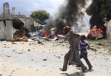A Somali girl and her brother run to safety near the scene of a blast in Mogadishu April 14, 2013. REUTERS/Feisal Omar