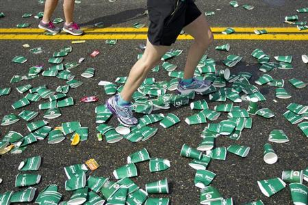 A runner steps over discarded cups near a water station in the 117th running of the Boston Marathon in Wellesley, Massachusetts April 15, 2013. REUTERS/Dominick Reuter