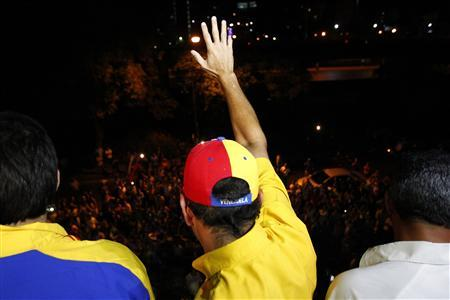 Venezuela's opposition leader Henrique Capriles (C) waves to supporters after a news conference at his campaign headquarters in Caracas April 15, 2013. REUTERS/Carlos Garcia Rawlins