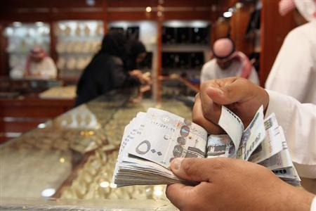 A salesman counts money at a jewellery shop at the gold market in Riyadh, March 11, 2013. REUTERS/Stringer/Files