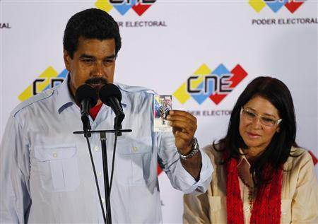 Acting Venezuelan President Nicolas Maduro holds a religious memento with a picture of late President Hugo Chavez, during a news conference with his wife Cilia Flores at the election commission in Caracas April 14, 2013. REUTERS/Carlos Garcia Rawlins