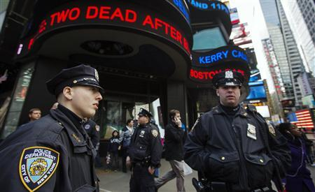 New York Police Department officers stand in the Times Square district of New York underneath a news ticker displaying details from fatal explosions in Boston, April 15, 2013. REUTERS/Lucas Jackson