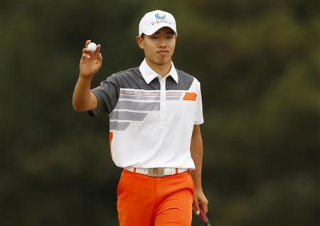 Amateur Guan Tianlang of China holds up his ball after sinking a par putt on the 18th green during final round play in the 2013 Masters golf tournament at the Augusta National Golf Club in Augusta, Georgia, April 14, 2013. REUTERS/Mark Blinch