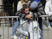 Девочку успокаивают после взрывов на 117-м Бостонском марафоне в Бостоне, штат Массачусетс, 15 апреля 2013 года. Трое человек погибли и более сотни получили ранения в результате двух взрывов в понедельник на финишной прямой Бостонского марафона, которые власти США сочли терактом. REUTERS/Jessica Rinaldi
