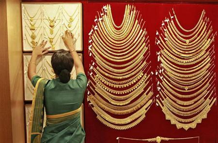 A saleswoman arranges a gold necklace inside a jewellery showroom in Kochi April 16, 2013. REUTERS/Sivaram V