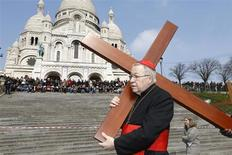 "French Archbishop of Paris Cardinal Andre Vingt-trois carries a cross in the gardens of the Montmartre's Sacre Coeur Basilica during the annual Good Friday ""Stations of the Cross"" procession in Paris March 29, 2013. REUTERS/Charles Platiau"
