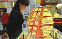 A customer looks at gold accessories at a gold store in Hangzhou, Zhejiang province April 16, 2013. REUTERS/China Daily