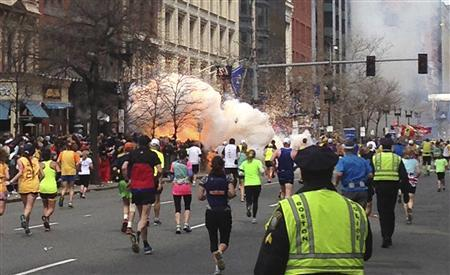 Runners continue to run towards the finish line of the Boston Marathon as an explosion erupts near the finish line of the race in this photo exclusively licensed to Reuters by photographer Dan Lampariello after he took the photo in Boston, Massachusetts, April 15, 2013. REUTERS-Dan Lampariello