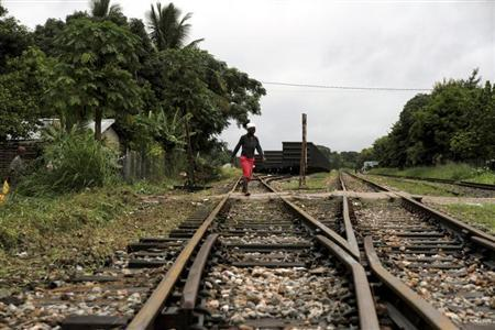 A woman crosses a railway line at Dondo, about 20km (12.4 miles) from Beira port, February 14, 2013. REUTERS/Agnieszka Flak