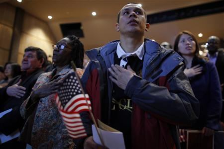 New U.S. citizens recite the U.S. Pledge of Allegiance during a naturalization ceremony for over 90 immigrants representing over 40 countries at Boston College in Chestnut Hill, Massachusetts March 21, 2013. REUTERS/Brian Snyder