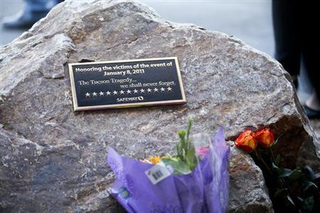 A plaque and flowers for victims of the January 8, 2011 Tucson shooting, are seen during a news conference at the Safeway grocery store parking lot where former congresswoman Gabrielle Giffords was shot during the incident in Tucson March 6, 2013. REUTERS/Samantha Sais