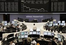 Traders work at their desks in front of the DAX board at the Frankfurt stock exchange April 12, 2013. REUTERS/Remote/Lizza David