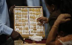 Покупатели выбирают золотые серьги в ювелирном магазине в Куала-Лумпур 17 апреля 2013 года. Цены на золото растут благодаря повышенному спросу на слитки, монеты и самородки после падения цен до двухлетнего минимума накануне. REUTERS/Bazuki Muhammad