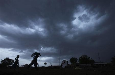 A girl runs for cover as it rains as monsoon clouds gather over Meerwada village in Guna district in Madhya Pradesh June 19, 2012. REUTERS/Adnan Abidi/Files