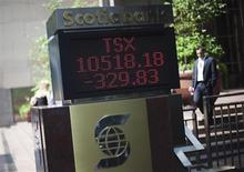 A man walks by a sign displaying TSX information in Toronto, August 17, 2009. REUTERS/Mark Blinch