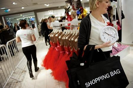A shopper holds a clock as she walks in the cordoned-off area of a Swedish fashion giant H&M store in Stockholm November 23, 2010. REUTERS/Jessica Gow/Scanpix