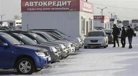 """Мужчины смотрят выставленные на продажу машины на авторынке """"777"""" под Красноярском 15 января 2013 года. Российский рынок автокредитования в 2012 году вырос на 20 процентов до $26 миллиардов благодаря послекризисному возвращению потребительской уверенности, но сейчас его подъем замедляется из-за ухудшения макроэкономических показателей и высоких процентных ставок, написала аудиторская компания Ernst & Young в исследовании авторынка РФ и СНГ. REUTERS/Ilya Naymushin"""