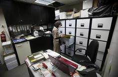 An employee stands in front of a file cabinet at Isra Software & Computer Co., an e-commerce firm in the West Bank city of Nablus April 8, 2013. REUTERS/Mohamad Torokman