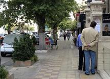 Pedestrians stop to read details of a death notice at a street in Damascus, April 3, 2013. REUTERS/Stringer