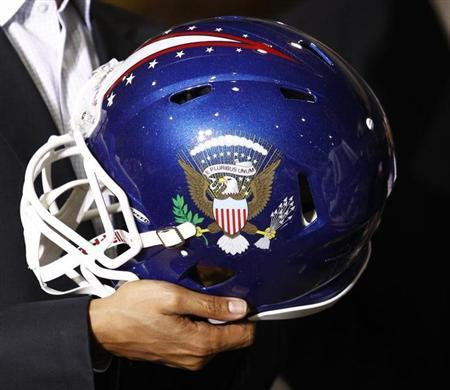 U.S. President Barack Obama holds a football helmet with the Presidential seal given to him during his visit to Riddell manufacturing facility in Elyria, Ohio January 22, 2010. REUTERS/Kevin Lamarque