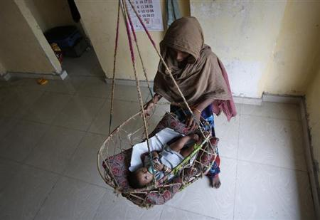 A woman tends to a baby sleeping in a hanging cot in the living room of a flat in an illegal building located next to the site of a building which collapsed last week in Thane district on the outskirts of Mumbai April 10, 2013. REUTERS/Vivek Prakash