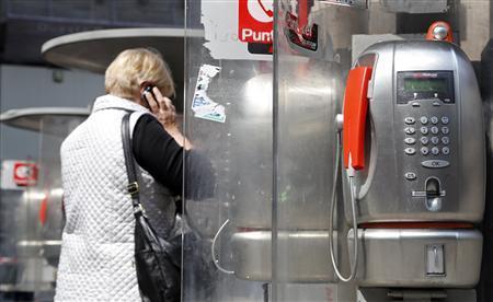 A woman walks near telephone booths in downtown Milan April 17, 2013. REUTERS/Stefano Rellandini