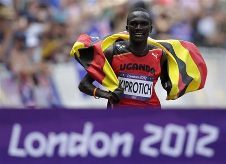 Uganda's Stephen Kiprotich celebrates with his national flag as he approaches the finish line to win the men's marathon in the London 2012 Olympic Games at The Mall August 12, 2012. REUTERS/Max Rossi
