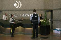 Royal Canadian Mounted Police (RCMP) officers stand in the headquarters of SNC Lavalin in Montreal April 13, 2012. REUTERS/Christinne Muschi