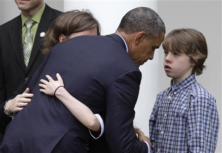 U.S. President Barack Obama listens to James Barden,13, as he hugs family members of Newtown victims after delivering a statement on commonsense measures to reduce gun violence in the Rose Garden of the White House in Washington April 17, 2013. REUTERS/Yuri Gripas