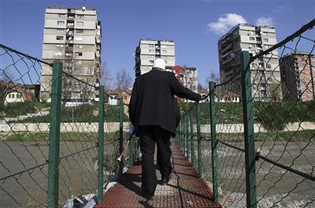 A man walks over a bridge in the ethnically divided town of Mitrovica April 17, 2013. REUTERS/Hazir Reka