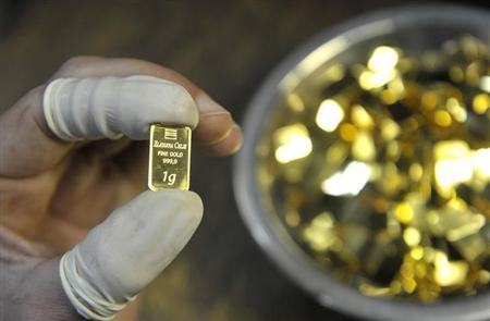 A worker inspects a one gram gold bar at the Zlatarna Celje in Celje, April 17, 2013. REUTERS/Srdjan Zivulovic