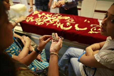A customer holds a gold necklace inside a jewellery showroom in Mumbai April 16, 2013. REUTERS/Danish Siddiqui